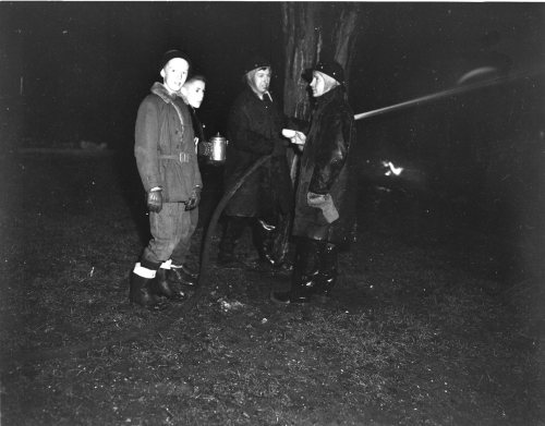 Bill Swann and L.D. Bowman offer coffee to firemen Doug Martin and Harold Hamilton